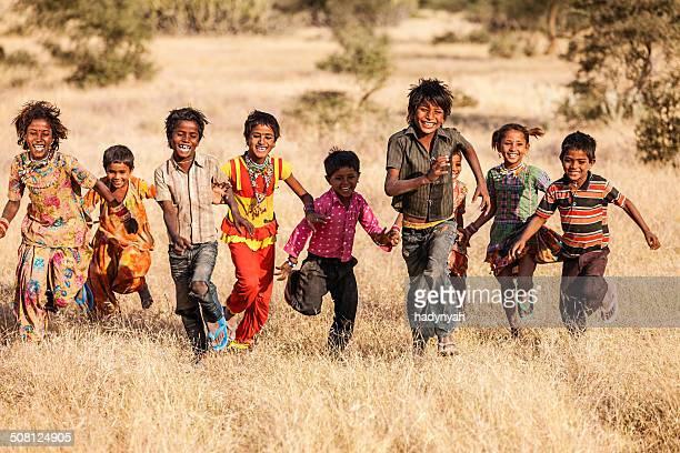 Group of running happy Indian children, desert village, India