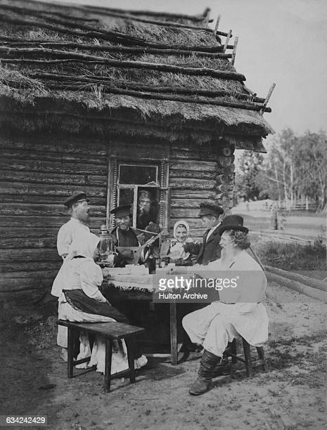 A group of Russian people drinking and playing the balalaika outside a cabin Russia circa 1915