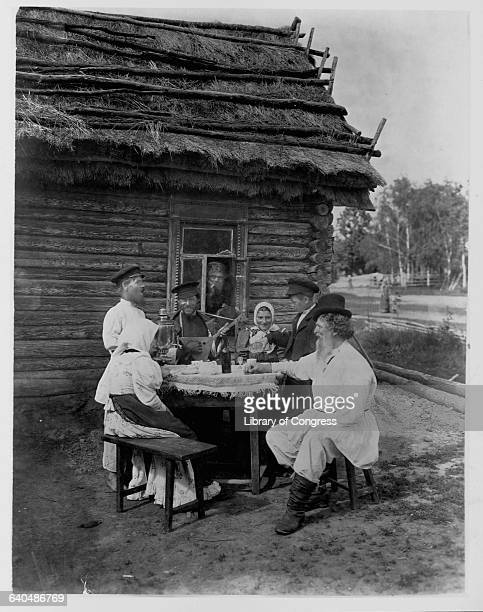 A group of Russians relax outside a log house with a thatched roof drinking and listening to the balalaika ca 1909