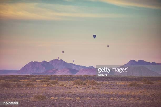 早朝のピンクの砂漠の風景の上にサファリ熱気球のグループ - セスリエム ストックフォトと画像