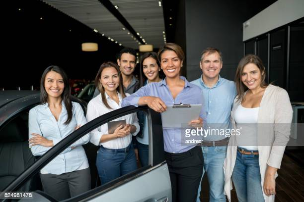 group of salespeople with happy customers at the car dealership - car salesperson stock pictures, royalty-free photos & images