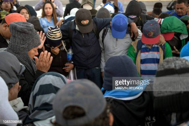 A group of Salvadoran migrants pray before starting their journey towards the United States in San Salvador on January 16 2019 A new caravan of some...