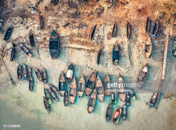 group of scattered small ships at chittagong port, bangladesh - bangladesh nature stock pictures, royalty-free photos & images