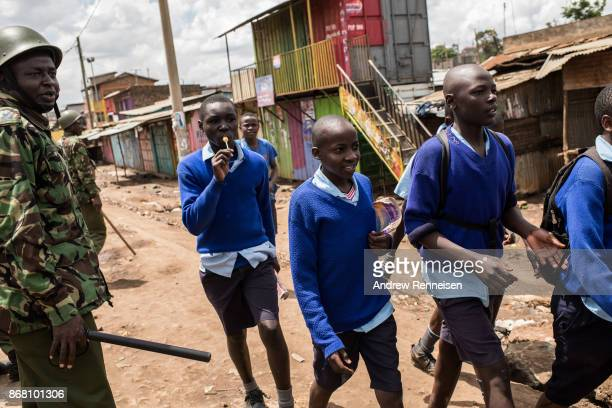 A group of school boys walk past police in the Kawangware slum on October 30 2017 in Nairobi Kenya Tensions remain high in Kenya after the...
