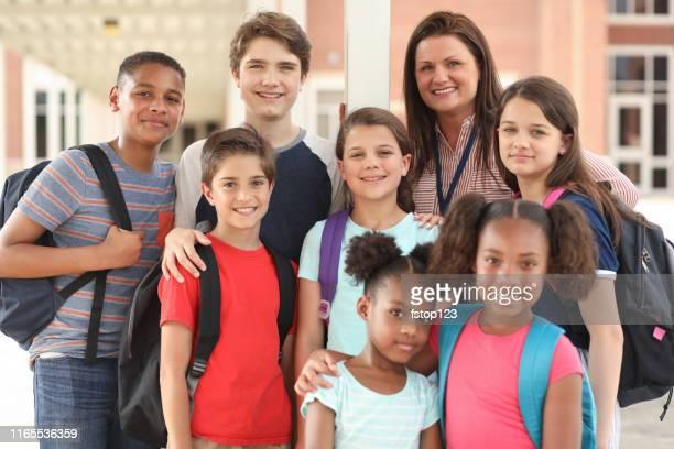 groep van schoolkinderen, vrienden en leraar op de campus. - gemengde leeftijdscategorie stockfoto's en -beelden