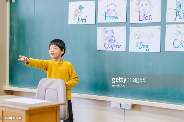 group of school children learning english while playing games - english language stock pictures, royalty-free photos & images