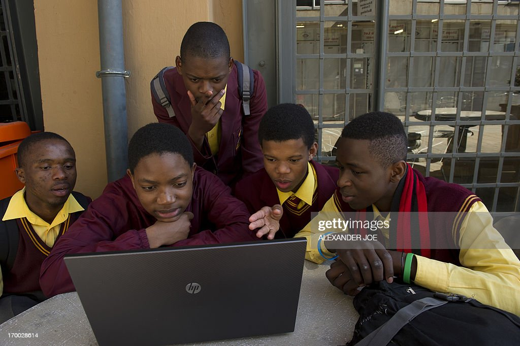 A group of school children play on a computer outside the hall where President of Microsoft International, Jean-Philippe Courtois announced a major partnership between Microsoft and the government's Jobs Fund to fast-track existing programmes to create jobs for the country's youth, in Joahannesburg on June 6, 2013.