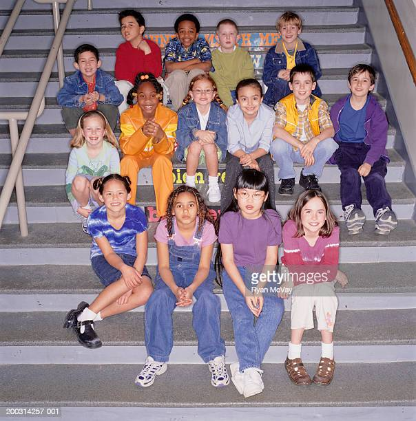Group of school children (8-9) sitting on stairs in school, portrait