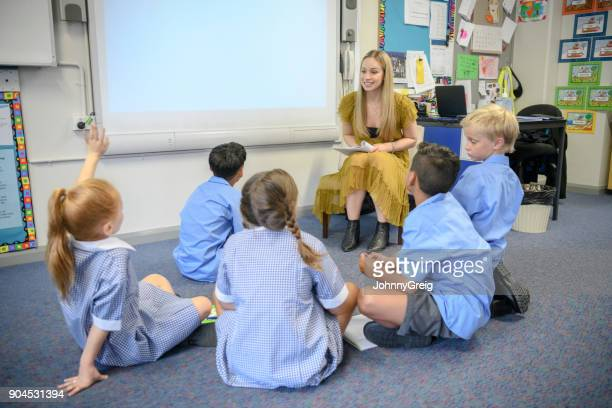 group of school children sitting on the floor listening to their teacher - teacher stock pictures, royalty-free photos & images