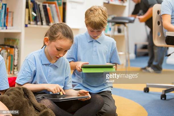 Group of school children using tablet computers in the library