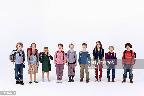 A group of school children wearing backpacks, standing in a row