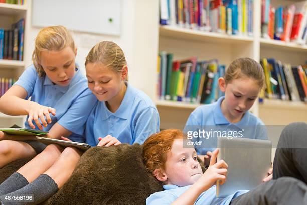 Groupe de filles de l'école à l'aide d'une tablette ordinateurs dans la bibliothèque