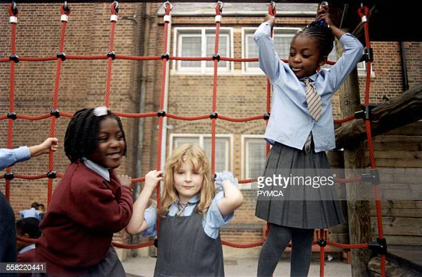 Group of school kids playing on a wooden climbing frame, South London, UK, 2000s.