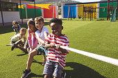 Group of school kids playing tug of war