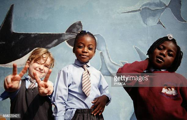Group of school kids standing in front of a mural, one girl giving the peace sign, South London, UK, 2000s.