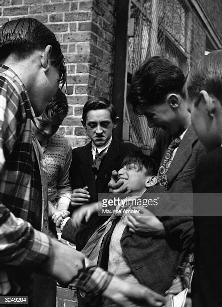 A group of schoolboys bullying a fellow pupil at a London school during filming of a documentary film Original Publication Picture Post 5932 Films...