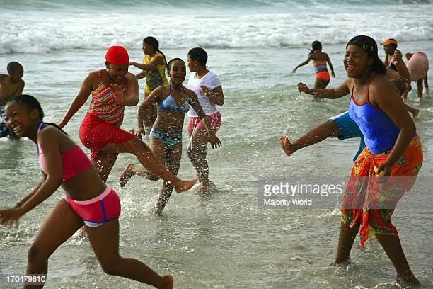A group of schoolchildren enjoying their first time ever at the ocean Camps Bay beach Cape Town South Africa October 9 2007
