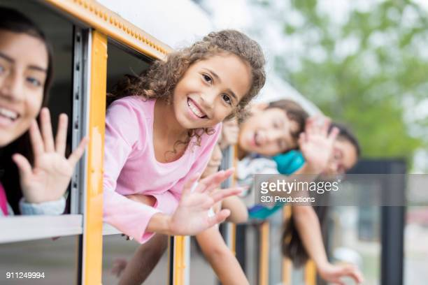 Group of schoolchildren hang out of windows on school bus