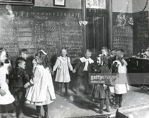 Group of schoolchildren hold hands in a circle as they play a game in their classroom, Keota, Iowa, early 1890s. The original caption identifies the...