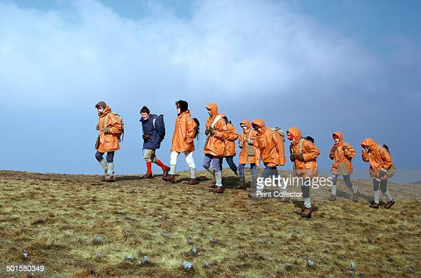 Group of schoolchildren in the Brecon Beacons on an outward bound exepedition near the top of Pen Y Fan. They are wearing protective clothing and...