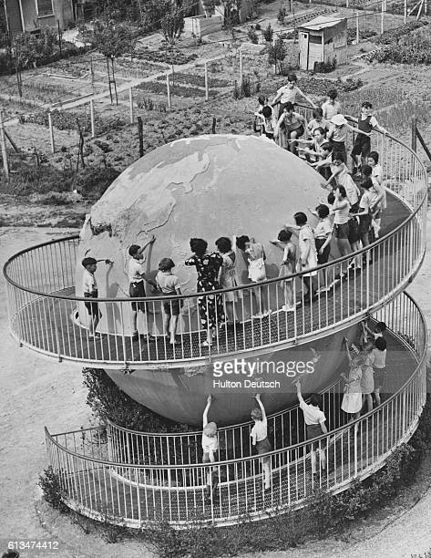 A group of schoolchildren look at a huge globe while standing on a curving ramp during a geography lesson at a school in Suresnes Paris