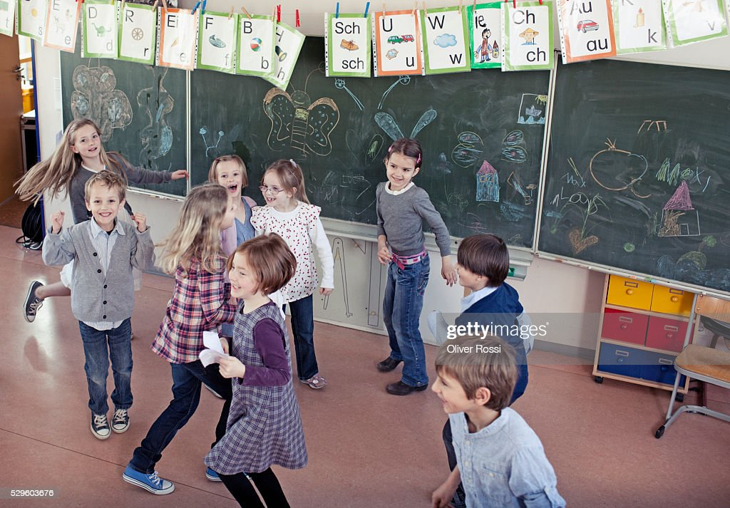 Group of schoolchildren (6-7) playing in classroom : ストックフォト