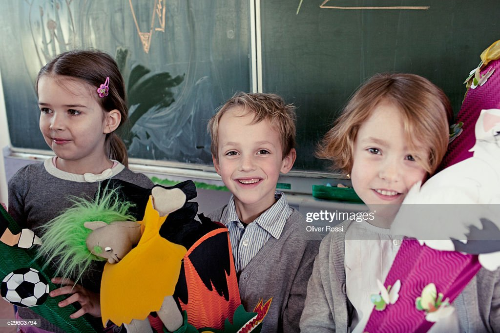 Group of schoolchildren (6-7) posing in front of blackboard with their toys : Stockfoto