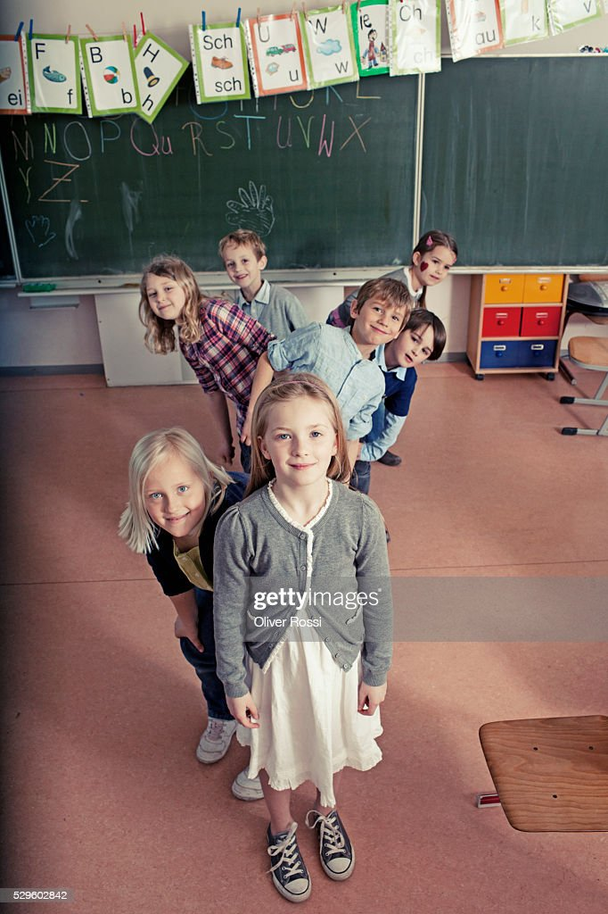 Group of schoolchildren (6-7, 8-9) posing together in classroom : Stockfoto