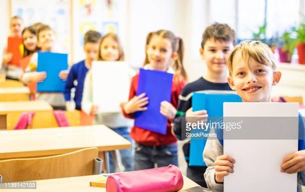 gruppo di scolari in piedi di fila e con in mano quaderni - solo bambini foto e immagini stock