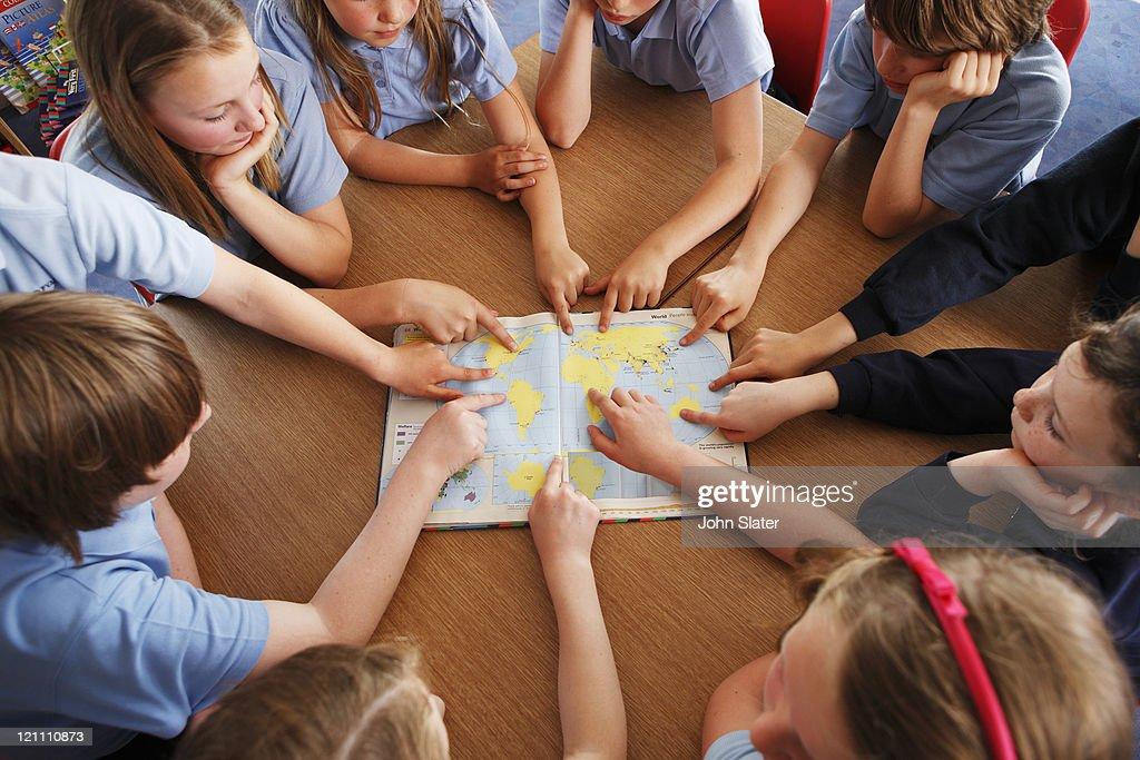 group of schoolchildren using atlas together : Foto de stock