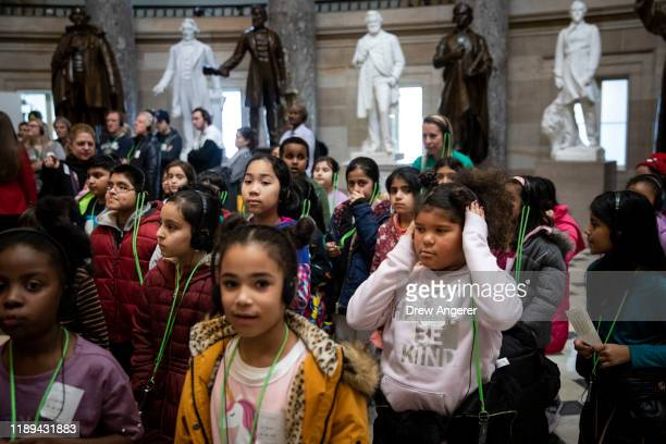 A group of schoolchildren walk through Statuary Hall while on a tour of the US Capitol as debate on the articles of impeachment against President...