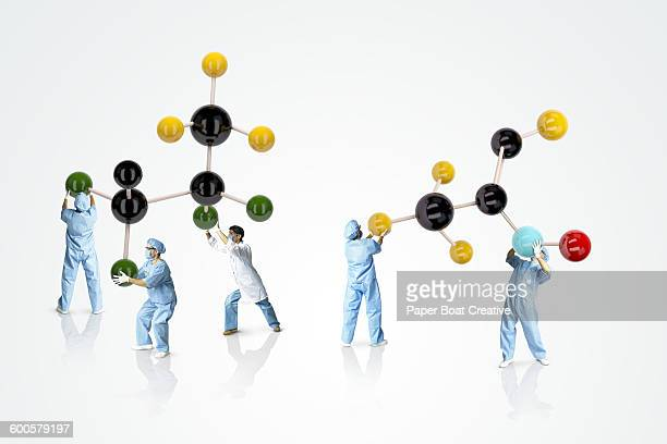 group of scientists holding up models of molecules