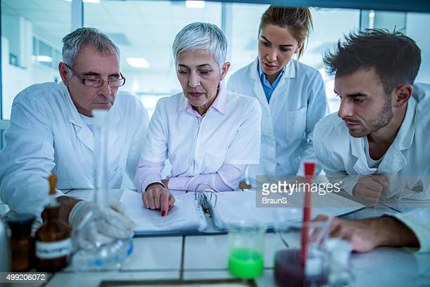 Group of scientists reading scientific data in the laboratory.