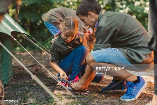 group of scouts building a tent - girl scout stock pictures, royalty-free photos & images