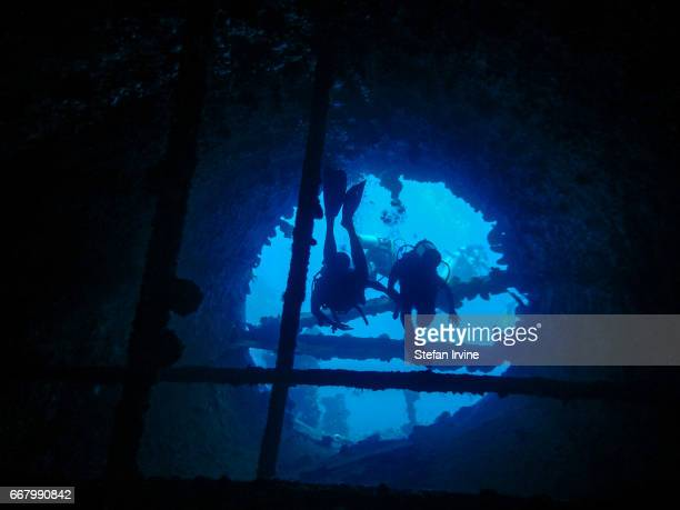 BUSUANGA PALAWAN PHILIPPINES A group of scuba divers explore an old ship wreck as they pass inside the funnel of a sunken ship in the Philippines