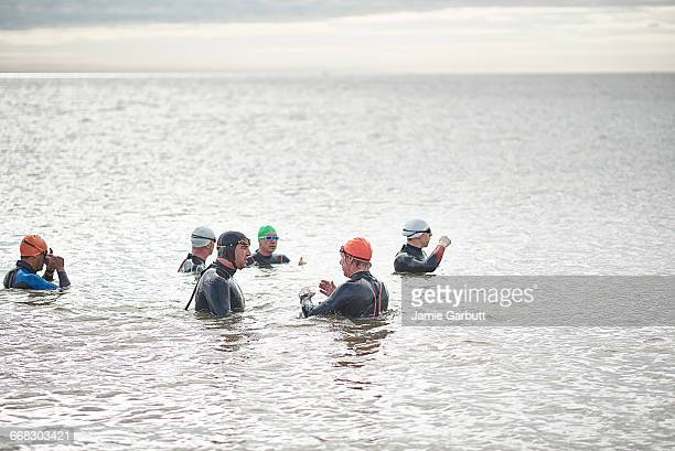 a group of sea swimmers stood in the sea talking - sea swimming stock pictures, royalty-free photos & images