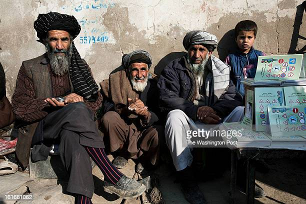 KABUL AFGHANISTAN – JANUARY A group of sellers sit outside the traffic department in Kabul On the right a pile booklets that explain the rules of the...