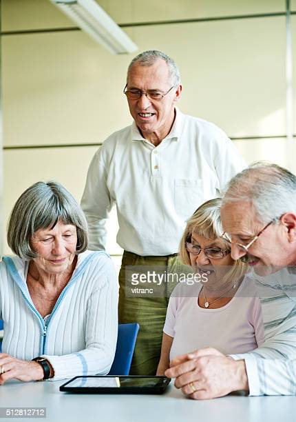 Group of senior adult having fun with digital tablet