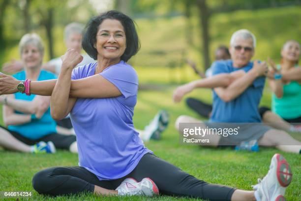 Eine Gruppe von älteren Erwachsenen nehmen eine Fitness-Calss draußen im Park. Sie sitzen auf dem Rasen und sind Strecken zusammen.