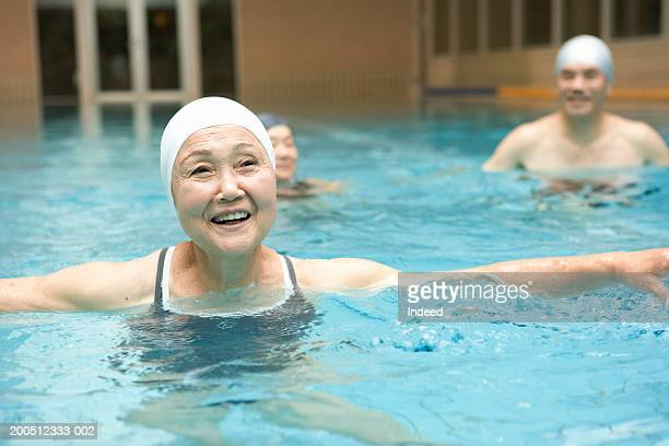 Group of senior adults exercising in swimming pool, smiling
