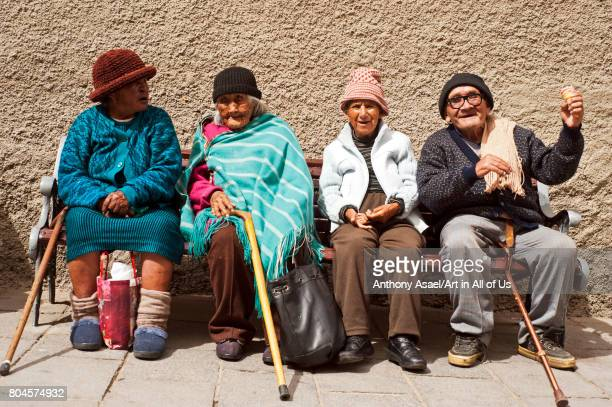 Group of senior adults sitting on bench and chatting on November 2016 in La Paz Bolivia