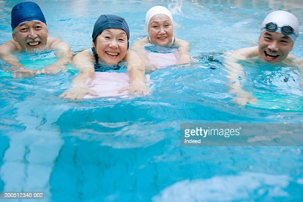 Group of senior adults swimming in pool, smiling, portrait