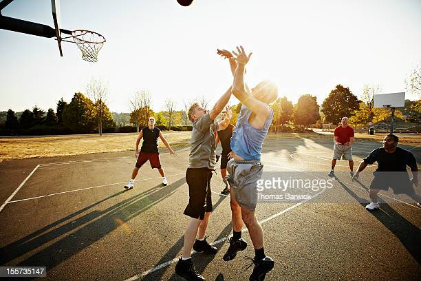 group of senior and mature men playing basketball - community spirit stock pictures, royalty-free photos & images