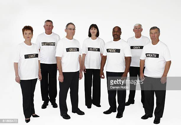 Group of senior business people wearing t-shirts with the seven deadly sins written on them