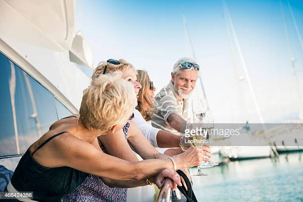 Group of senior friends drinking wine on a yacht