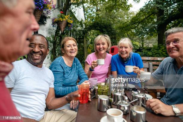 group of senior friends enjoying a tea break - tea room stock pictures, royalty-free photos & images