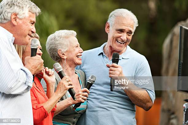 group of senior friends having a party - karaoke stock pictures, royalty-free photos & images
