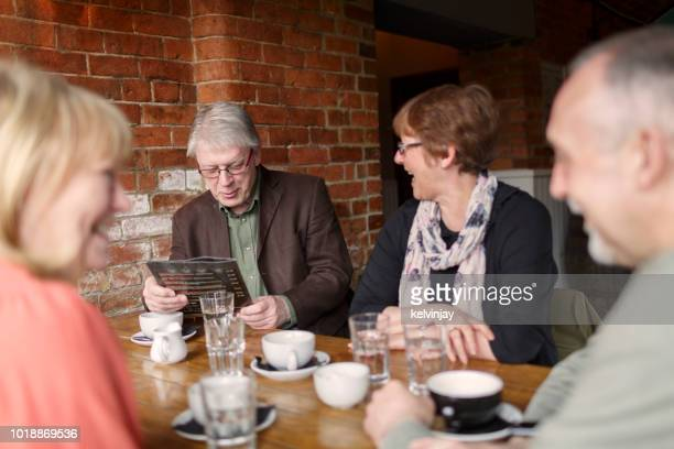A group of senior friends having fun and drinking coffee in a bar