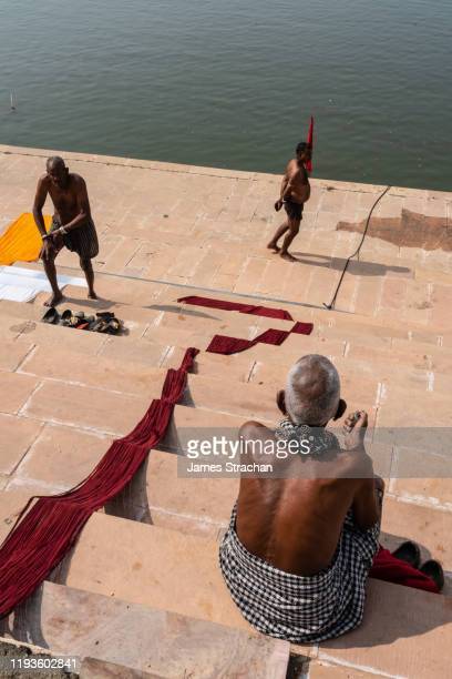 group of senior men relaxing on the ghats (steps leading to the water) after bathing in sacred pushkar lake with red, white and yellow turbans unfurled to dry, pushkar, rajasthan, india - men stockfoto's en -beelden