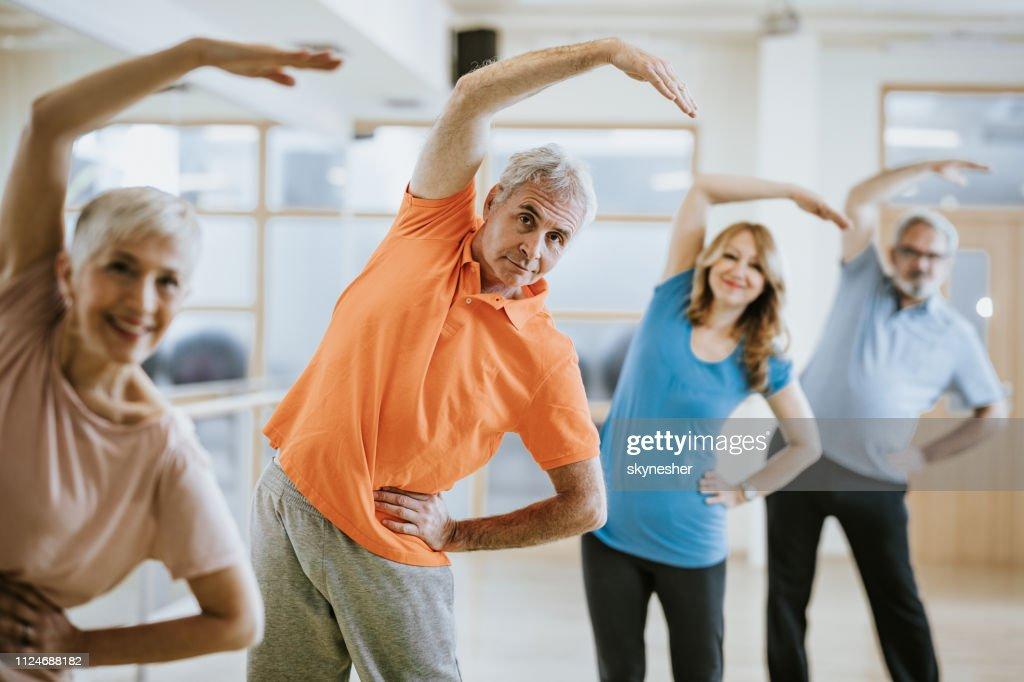 フィットネス センターでストレッチ体操を行う高齢者のグループです。 : ストックフォト